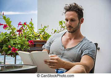 Handsome athletic young man reading book outside sitting on...