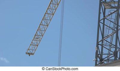 Crane on blue sky background. Ropes hanging from jib crane....
