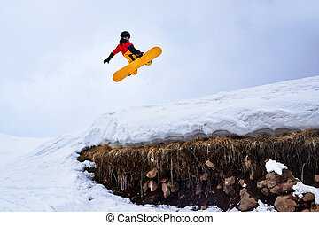 Snowboarder jumping from springboard on a snowy hill with...