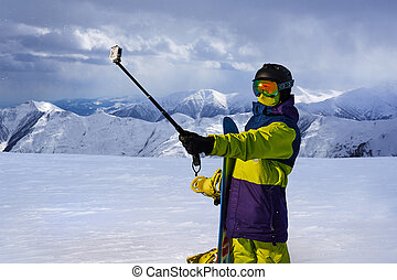 Snowboarder doing selfie on action camera stick -...