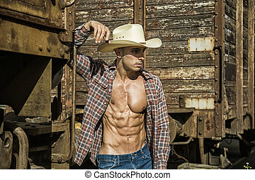 Sexy topless cowboy posing against old train - Portrait of...
