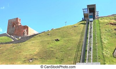 Funicular moving down the hill. Ruined building in the...