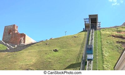 Funicular moves up the hill. Ruins in the distance. Tour...