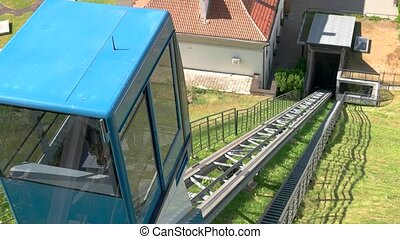 Small funicular moves downhill. Rails leading into the...