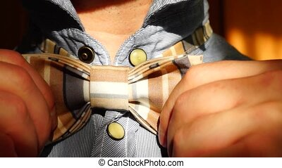 Man ties bow tie - Man ties and corrects the bow tie