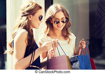 happy women with shopping bags at shop window - sale,...
