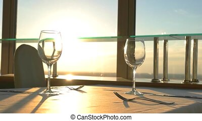 Empty wineglasses and cutlery. Sky at sunset. Revolving...