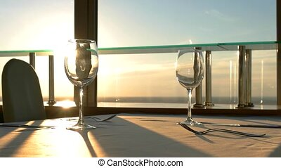 Empty wineglasses on the table. Sunset sky behind the...