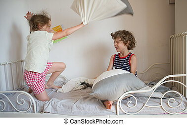 Brother and sister have arranged fight by pillows on a bed...
