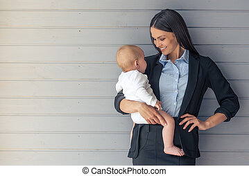 Business lady with her baby - Portrait of beautiful business...