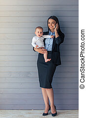 Business lady with her baby - Full length portrait of...