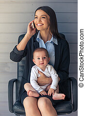 Business lady with her baby - Beautiful business lady in...