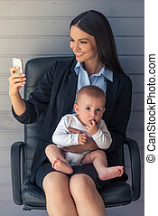 Business lady with her baby - Beautiful business lady is...