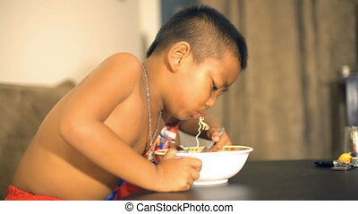 Little Thai boy eating instant noodles
