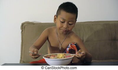 Little Thai boy enjoying instant noodles
