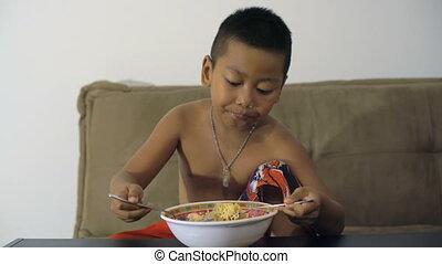 Little Thai boy enjoying instant noodles