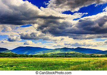 field under clouds - field in front of the mountains under...