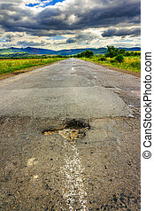 hole on mountain highway - broken highway with hole in the...