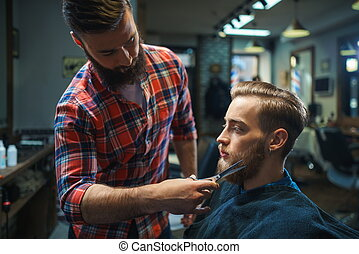 Customer in a barber shop - Young bearded man in a barber...