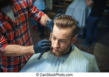 In a barber shop - Young bearded man in a barber shop