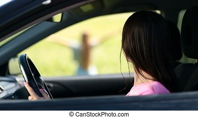 View through car window on woman standing in field - View...