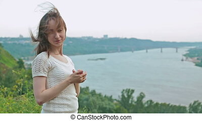 Young woman in embankment, hair blowing in wind