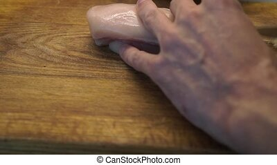 Male hands filet chicken on a wooden cooking board