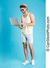 Full length of happy young man standing and using laptop