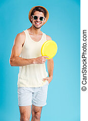 Happy young man in hat and sunglasses holding frisbee disk