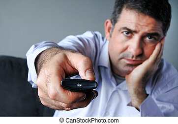 Upset and bored man holding tv remote control zapping TV...