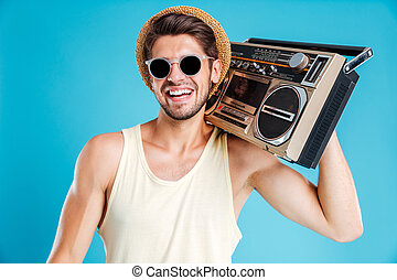Happy young man in hat and sunglasses with boombox - Happy
