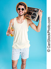 Smiling handsome young man with boombox and bottle of beer