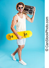 Smiling man with yellow skateboard walking and holding old...