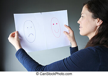 Young woman choosing between happiness and sadness