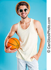 Cheerful young man in hat and sunglasses holding basketball...