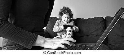 Mother works on laptop while her child plays on smartphone...