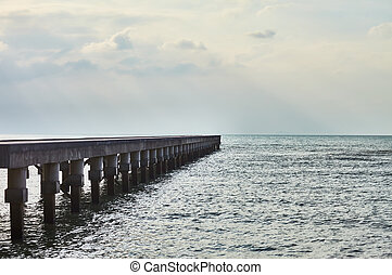 wooden pier with sun rays over sea