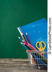 School supplies in a backet - School supplies on a wooden...