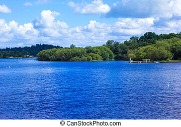 People rowing canoe paddling in calm blue Loch Lomond lake...