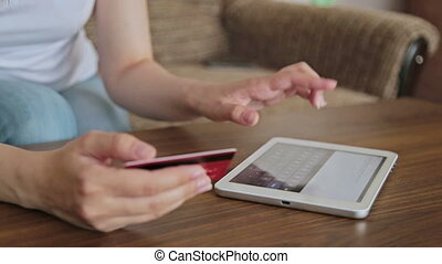 Womans hands typing security code from credit card - Female...