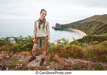 woman hiker looking aside in front of ocean view landscape -...