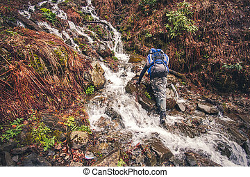Man Traveler with backpack crossing waterfall in mountains...