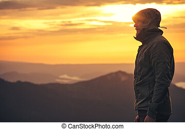 Young Man standing alone outdoor with sunset mountains on...