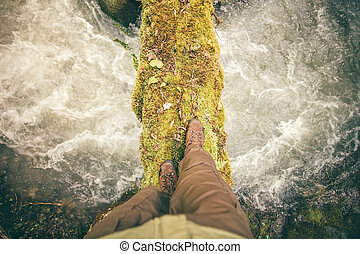 Feet Man trekking boots hiking outdoor with river and stones...