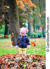 happy little girl playing with leaves