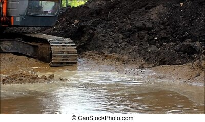 excavator bucket to draw water in the flooded ditch at a construction site for road repair.