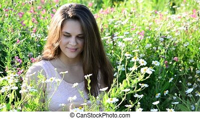 girl tells fortunes on a camomile flower on the meadow -...