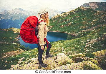 Young Woman with red backpack mountaineering Travel...