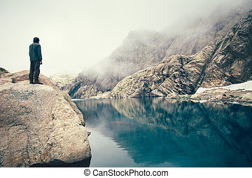 Man Traveler standing alone on stone cliff lake and misty...