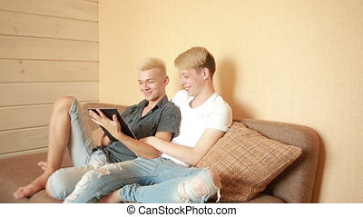 Happy gay couple using tablet in bed. gay couple - Happy gay...
